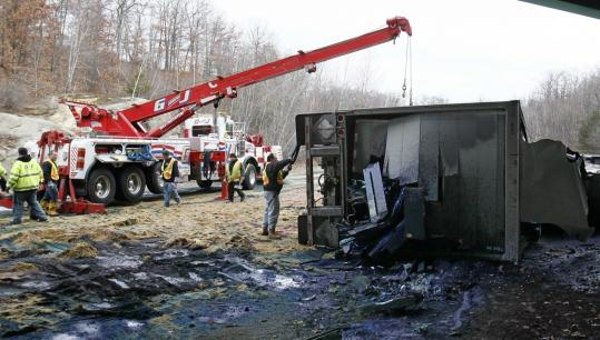 Workers prepared to right the tractor-trailer that overturned on the ramp to Interstate 95 North in Peabody yesterday.