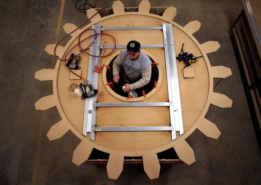 At Mystic Scenic Studios, cabinet maker Sean Groom works on a huge gear that will be painted and hung from a ceiling for a client in Lowell.