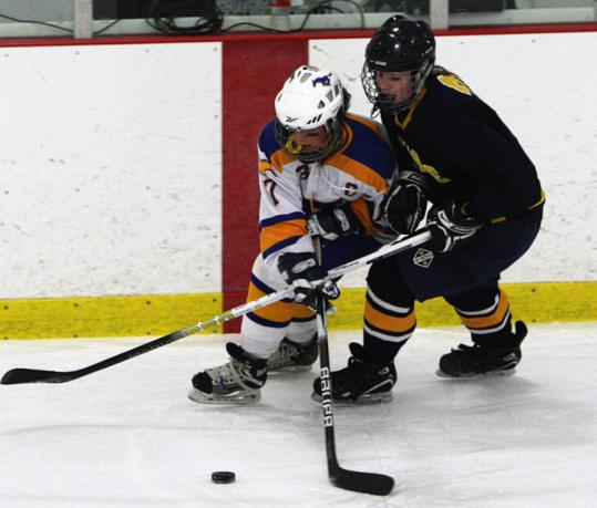 Norwood&#8217;s Taylor Donners (left) battles with Fontbonne&#8217;s Maggie Leary for a loose puck during the Ducks&#8217; 3-2 victory.