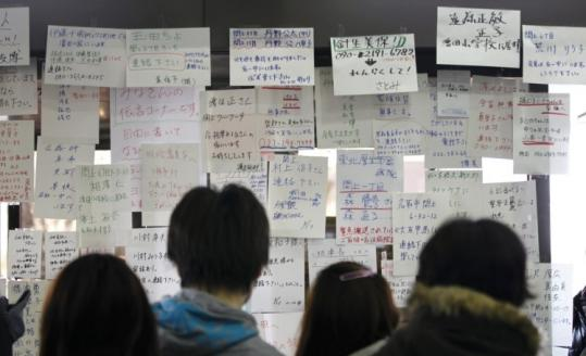 Japanese residents searched for the names of their missing family members yesterday at a temporary information center.
