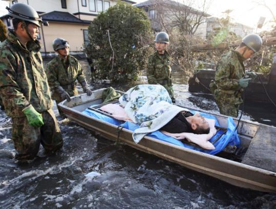 Rescue workers moved an elderly man who survived being buried under rubble in Miyagi Prefecture yesterday, three days after the devastating earthquake and tsunami.
