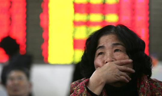 An investor watched the stock price board at a private securities company yesterday in Shanghai.