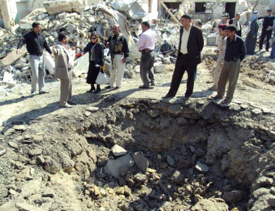 Iraqis inspected a crater left after a suicide bomber attacked an Iraqi Army intelligence battalion headquarters yesterday.