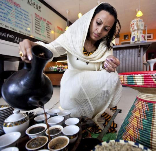Co-owner Netsanet Woldesenbet pours coffee at Lucy Ethiopian Cafe and Restaurant.