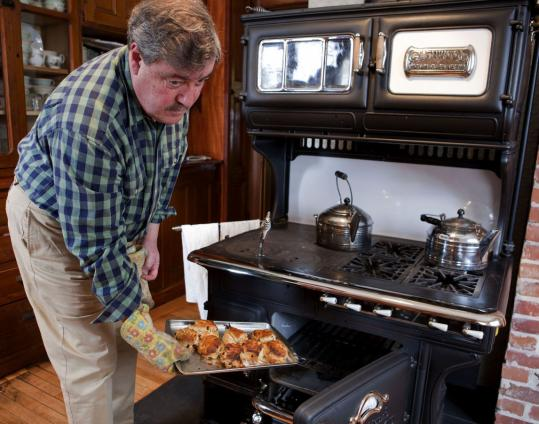 John Buscemi bakes scones in his Gold Medal Glenwood. Two burners are set over coals; four are gas-fired. He says heat is more evenly distributed in the coal oven than in modern ovens.