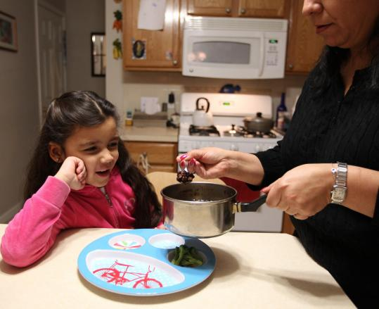 Rosa Aguirre of Everett serves her daughter, Sofia Blandino.