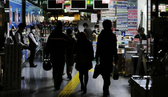 Customers walked in a store with fewer lights switched on to conserve energy during rolling blackouts in Tokyo yesterday.