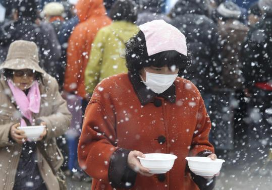 Evacuees brought food from a soup kitchen back to their makeshift shelter in Minamisanriku, northern Japan, yesterday.