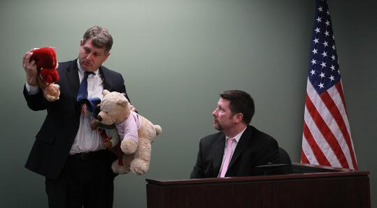 Middlesex Assistant District Attorney Daniel Bennett shows stuffed animals, taken from a Harvard dorm room, to Cambridge Police Officer John Crowley in court yesterday.