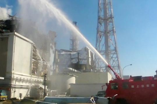 A firetruck doused a reactor at the Fukushima Daiichi nuclear power station in Japan. Six workers there were exposed to more than 100 millisieverts of radiation.