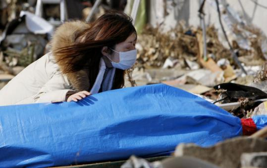 Tayo Kitamura yesterday knelt in the street by the body of her mother, found in the ruins of the woman's Onagawa home.