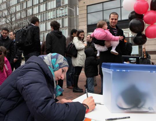 Harvard graduate student Mariam Mahmoud (left) cast a symbolic vote on Egypt's constitutional referendum yesterday in Harvard Square.