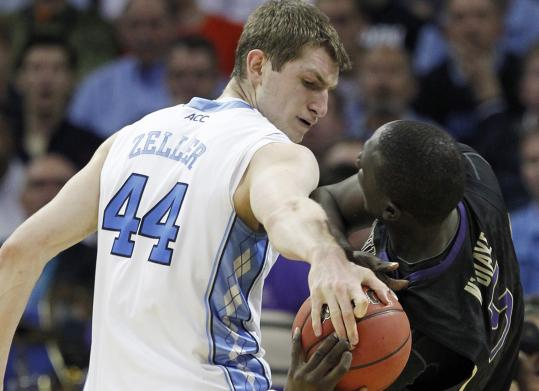 North Carolina's Tyler Zeller tries the strong-arm approach as he attempts to steal the ball from Washington's Aziz N'Diaye.