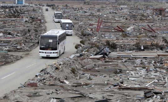 Buses took residents through their devastated suburb in Miyagi Prefecture yesterday. The death toll rose to more than 8,600.