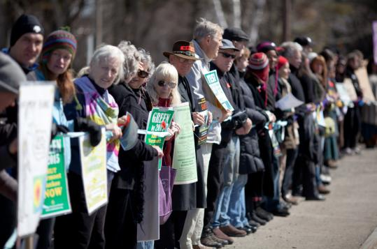 Protesters lined the road outside the Vermont Yankee nuclear power plant in Vernon Sunday during a vigil in solidarity with victims of the Japanese nuclear plant crisis. State legislators must approve Vermont Yankee's request to extend its license.