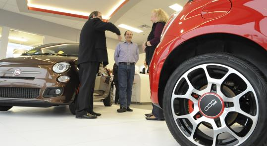 Angelo Falcone (center) of Acton and his wife, Rhonda, chatted with a salesman as they waited for the new Fiat at Kelly Fiat in Peabody.