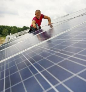 A worker fixed solar panels at a generating park in Germany in August. The nation plans to boost alternative-energy use.