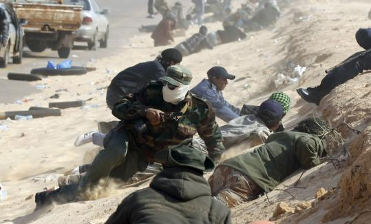 Rebel fighters in Libya took cover during a shelling along a road near the strategic city of Ajdabiya yesterday.
