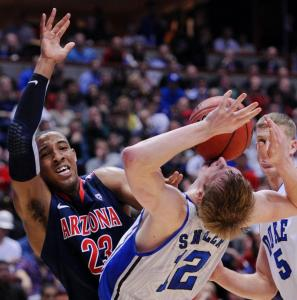 Arizona's Derrick Williams, who finished with a career-high 32 points, draws contact from Duke forward Kyle Singler.