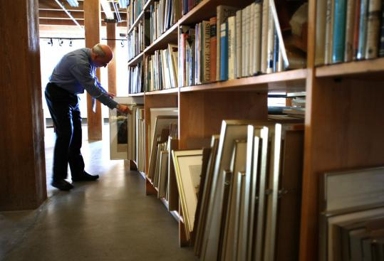 At Ars Libri, a bookseller in the South End, Elmar Seibel, the owner, looks into a shelf of framed prints from a collection.