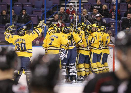 A happy pack of Wolverines swarm around Kevin Lynch after the sophomore scored 2:35 into overtime in Michigan's victory over Nebraska-Omaha.