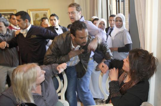 A journalist tried to stop a Libyan Ministry of Information official from grabbing Eman al-Obeidy (bottom right).