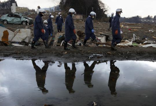 Japanese rescue teams combed the rubble yesterday in Kensennuma, looking for bodies from the March 11 earthquake.