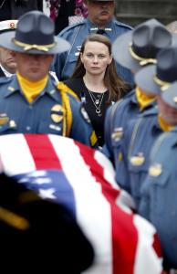 Surrounded by other officers, Melissa Christian followed the coffin of her 34-year-old husband after a memorial service yesterday in Athens, Ga. A suspect in the officer's death is in custody.