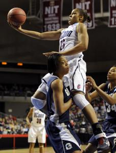 UConn's Maya Moore (23 points) soars over Georgetown's Adria Crawford in the first half.