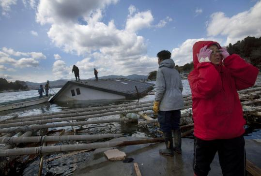 Reiko Kikuta (right) and her husband, Takeshi, waited on the shore of Oshima Island in northeastern Japan yesterday as workers attempted to attach ropes to their submerged home to try to pull it ashore using construction equipment.