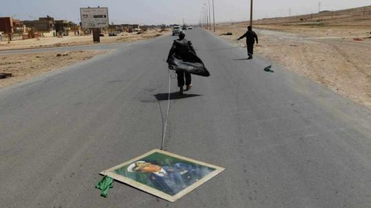 A rebel fighter dragged a picture of Libyan leader Moammar Khadafy yesterday along a road in Bin Jawad. The rebel advance was halted yesterday just past the town by government troop fire.
