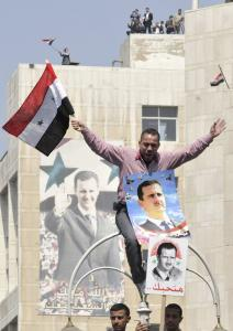 A progovernment demonstrator waved the national flag and displayed posters of President Bashar Assad during a rally at the central bank square in Damascus.