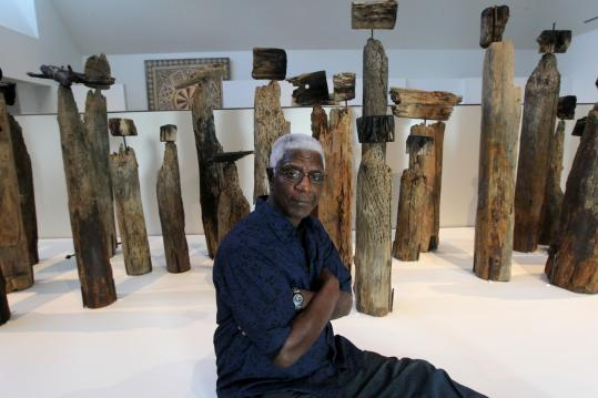El Anatsui with one of his sculptures in a career retrospective at the Davis Museum at Wellesley College.