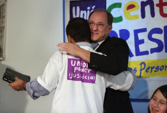 After he addressed a rally in East Boston yesterday, US Representative Luis V. Gutierrez (in T-shirt) received a hug from his colleague Michael E. Capuano. Both Democrats want President Obama to change US immigration policy.