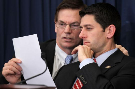 House Budget Committee chairman Paul Ryan (right), with an aide, proposed big cuts in the budget introduced to his panel.