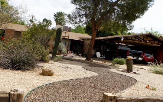 This Phoenix property has a desert front lawn instead grass; the latter can be costlier in part because of watering requirements. Also, homeowners' associations in this arid region typically have rules requiring residents to maintain either desert landscaping or green grass — brown lawns are not an option.