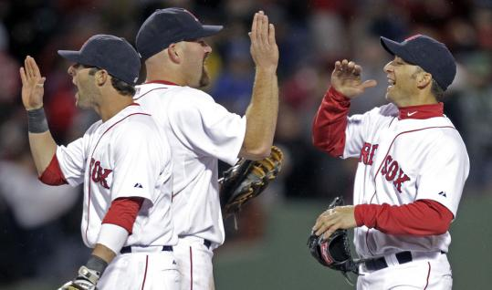 Red Sox infielders Dustin Pedroia, Kevin Youkilis, and Marco Scutaro are up in arms as they celebrate a victory over the Yankees.