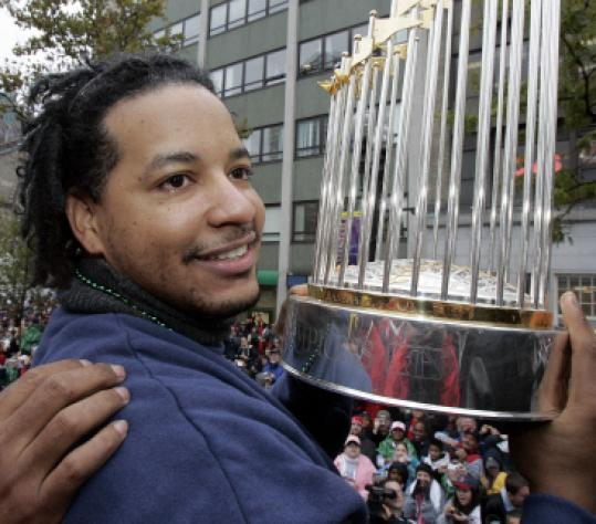 2004 World Series MVP Manny Ramirez shows off the World Series trophy to Boston fans.