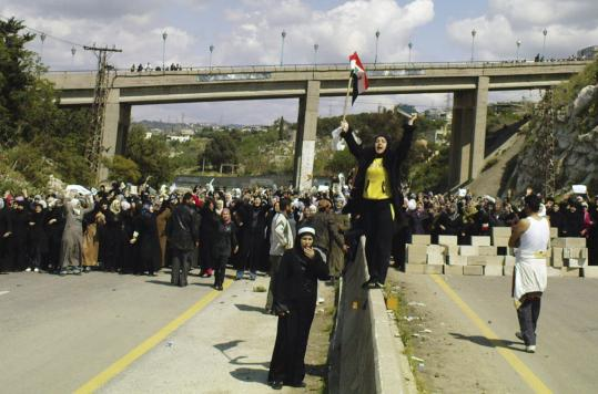 Thousands of women and children holding white flags and olive branches blocked a highway yesterday in Banias, Syria, demanding the release of men who were rounded up in recent days.