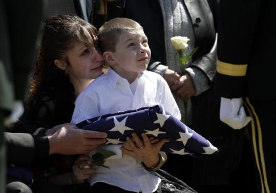 Nikolous Poulin, 5, sat in the lap of his aunt, Jennifer Poulin, yesterday at the funeral for his father, Massachusetts National Guard Specialist Dennis Poulin of Pawtucket, R.I.