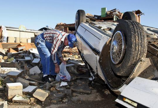 Jerome Whittington tried to salvage his belongings from his car in Tushka, Okla., yesterday, after a tornado hit