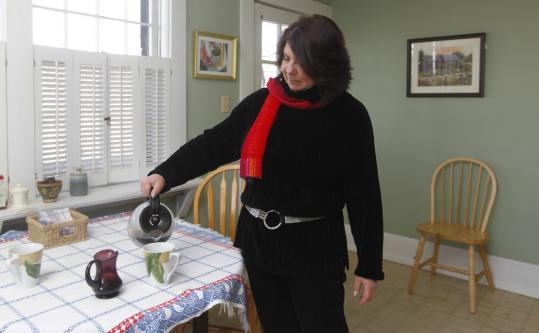 Candace Julyan pours a beverage in the Malden guest house she runs with her husband.