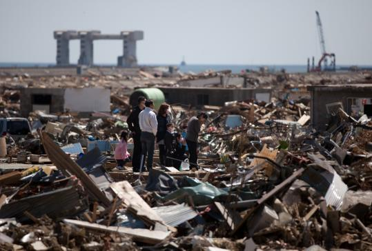 A family in the midst of devastation in Rikuzentakata, Japan, prayed yesterday for victims of last month's tsunami.