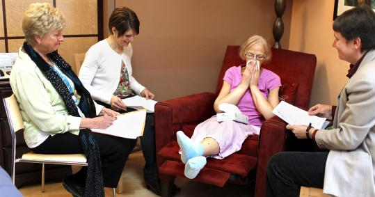 Sandra Ashe (second from right) becomes emotional as members of the Threshold Choir, (from left) Judy Whitney, Patty Ramsden, and Lisa Kynvi, sing to her at the Merrimack Valley Hospice House in Haverhill.