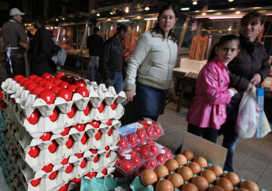 Athenians shopped in a central market in Greece's capital yesterday, many of them preparing for Easter celebrations on Sunday. But strict cutbacks last year mean less money is being spent.