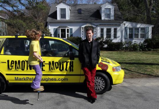 Mark Peter Hughes, with daughter Zoe, stood outside his Wayland home by the van in which his family drove 13,000 miles to promote his book.