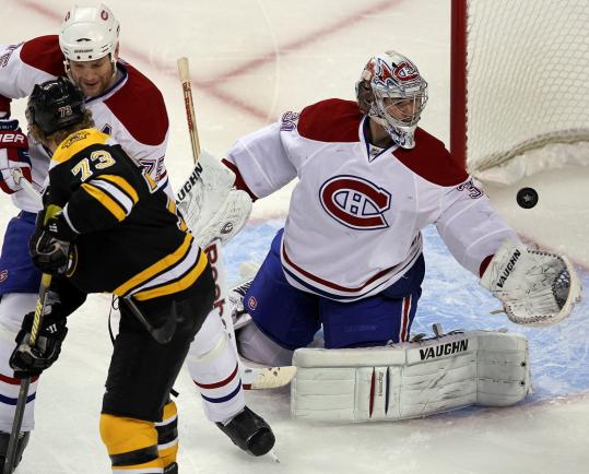 Carey Price gets a glove on Michael Ryder's first-period scoring bid as Canadiens defenseman Hal Gill clears out the crease.