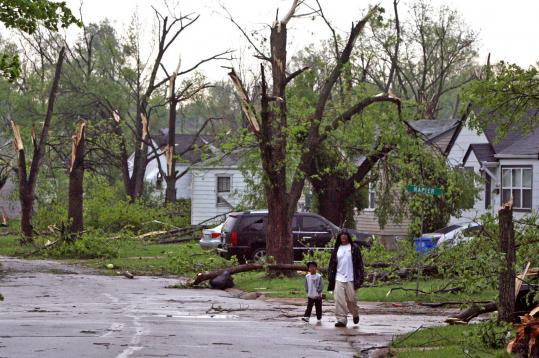 Residents of Berkeley, Mo. viewed damage from a tornado that hit the St. Louis area on Saturday, destroying up to 100 homes.