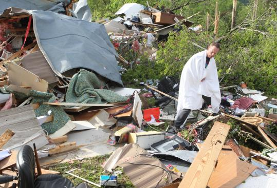 A resident of Garland County, Ark., looked for his cellphone yesterday in the remains of his home after a tornado hit the area.