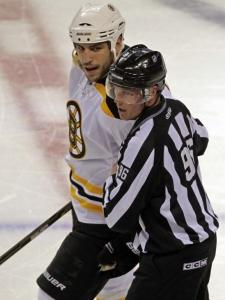 Milan Lucic is escorted off after being thrown out of the game for boarding Jaroslav Spacek.